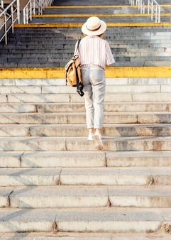 Mujer de vista posterior caminando por las escaleras