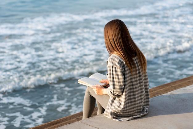 Mujer de vista posterior leyendo junto al mar