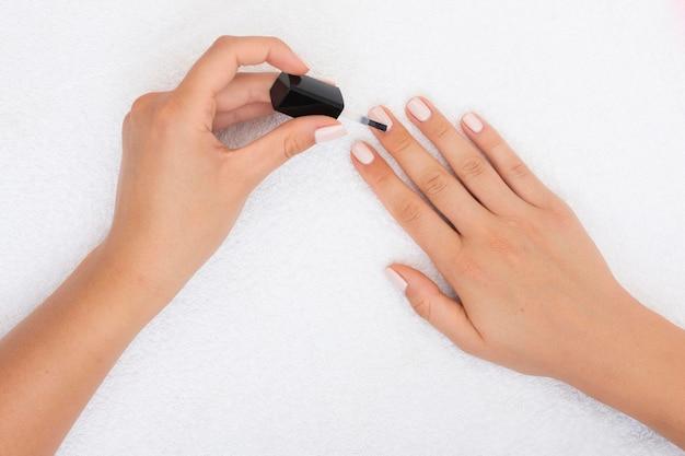 Mujer de vista superior aplicando esmalte de uñas