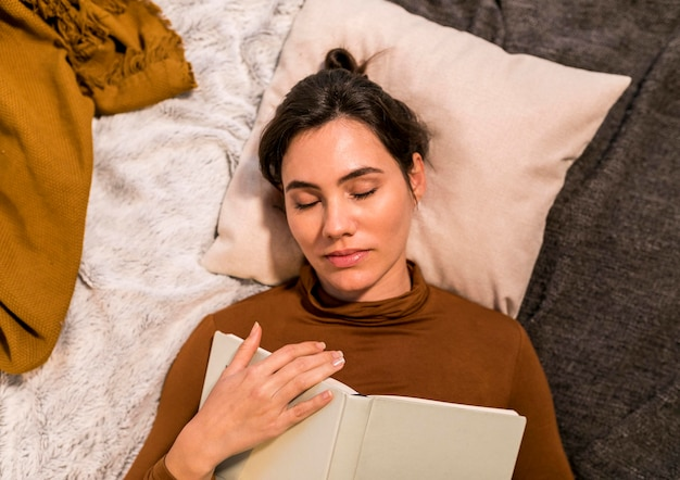 Mujer de vista superior durmiendo después de leer un libro