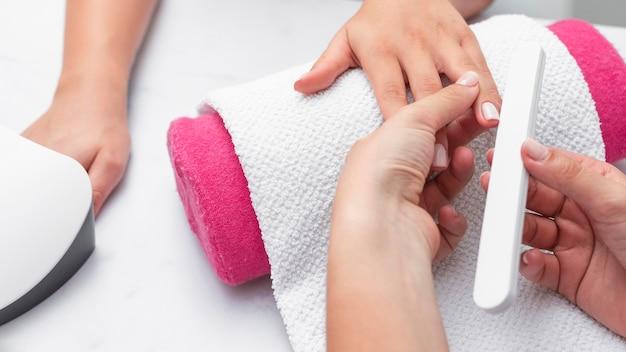 Mujer de vista superior haciendo la manicura de un cliente