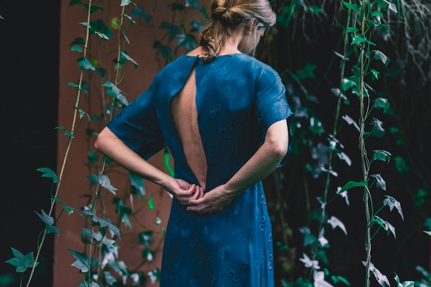 Mujer de vista trasera cerca de casa con hiedra