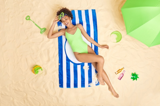Mujer viste bikini verde y gafas de buceo se encuentra en una toalla de rayas azules disfruta de las vacaciones de verano pasa el tiempo libre en la playa de arena toma el sol durante el día soleado. vacaciones.
