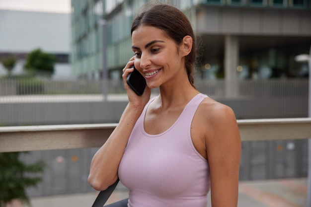 La mujer viste una camiseta informal, utiliza el teléfono móvil para comunicarse, disfruta de una conversación amistosa, sonríe suavemente, camina sobre la ciudad.