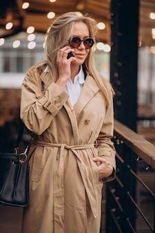 Mujer vistiendo abrigo beige y caminando por la calle en navidad