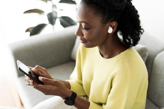 Mujer vistiendo auriculares inalámbricos y usando un teléfono móvil