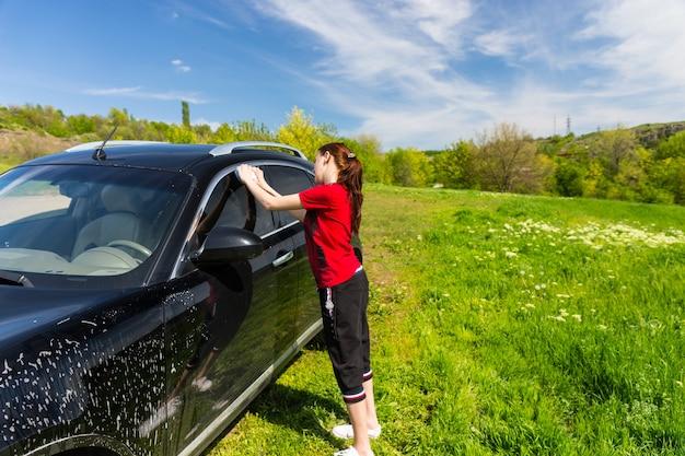 Mujer vistiendo camisa roja lavado de vehículos de lujo negro en campo con esponja jabonosa en día soleado