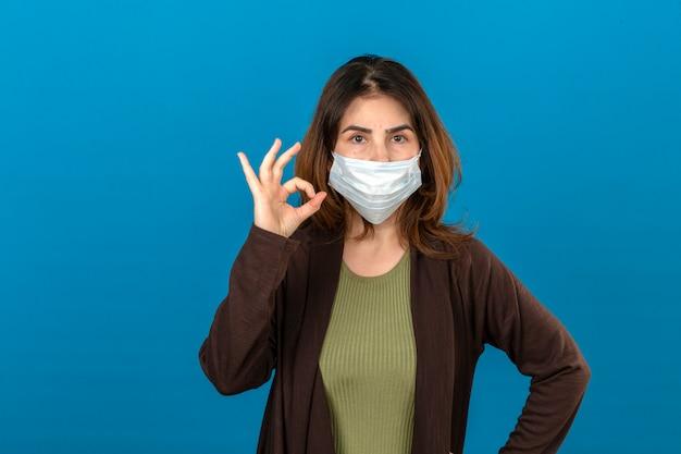 Mujer vistiendo chaqueta marrón en máscara protectora médica buscando confianza haciendo aceptar firmar de pie sobre la pared azul aislada
