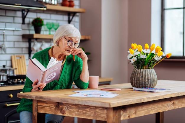 Mujer vistiendo elegante cárdigan verde y gafas sosteniendo un libro de la santa biblia abierta