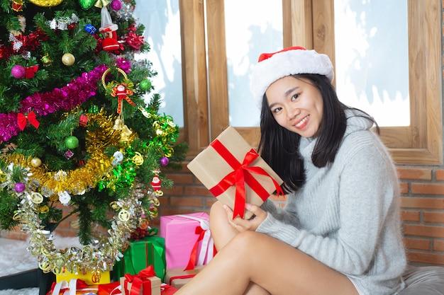 Mujer vistiendo gorro de navidad feliz con regalo de navidad