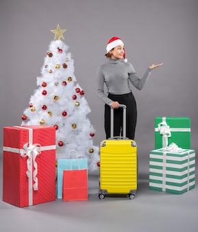 Mujer vistiendo gorro de papá noel con equipaje junto al árbol de navidad