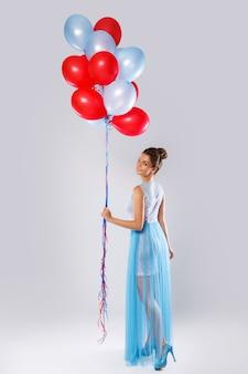 Mujer vistiendo un hermoso vestido con muchos globos de colores