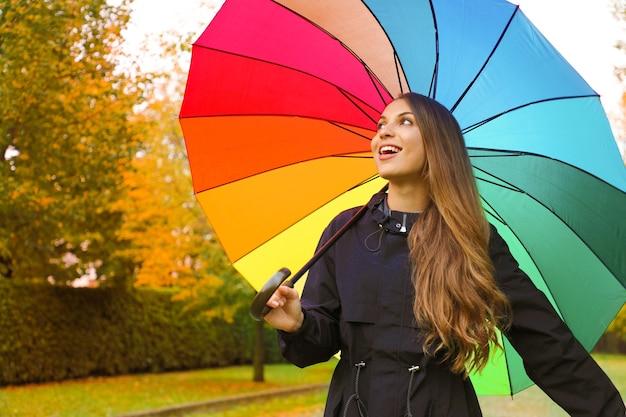 Mujer vistiendo impermeable oscuro bajo el paraguas del arco iris en el parque de la ciudad