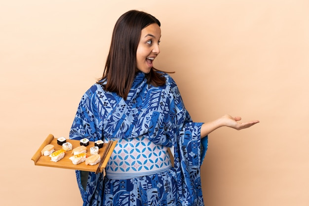 Mujer vistiendo kimono y sosteniendo sushi sobre aislado con expresión de sorpresa mientras mira hacia el lado