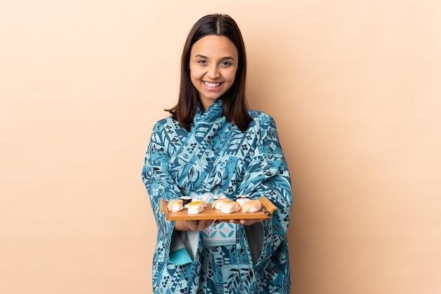 Mujer vistiendo kimono y sosteniendo sushi sobre aislado
