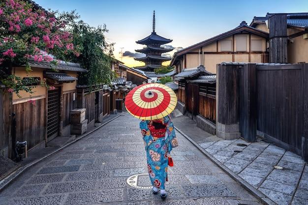 Mujer vistiendo un kimono tradicional japonés con paraguas en la pagoda yasaka y la calle sannen zaka en kyoto, japón.