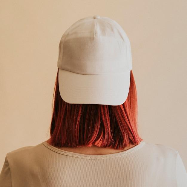 Mujer vistiendo una maqueta de gorra blanca
