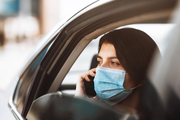 Mujer vistiendo una máscara médica estéril en un taxi en un asiento trasero mirando por la ventana hablando por teléfono