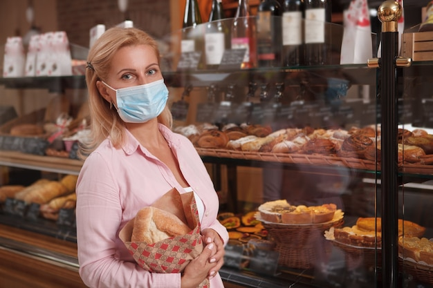Mujer vistiendo mascarilla médica, comprando pan en la panadería local, espacio de copia