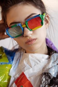 Mujer vistiendo plástico sobre fondo blanco. modelo femenino en ropa y zapatos hechos de basura.