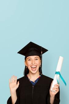 Mujer vistiendo regalia sosteniendo su título de graduación