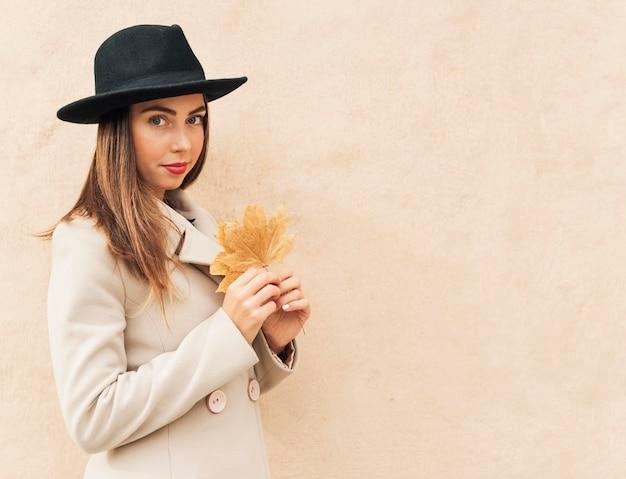 Mujer vistiendo un sombrero negro y sosteniendo una hoja
