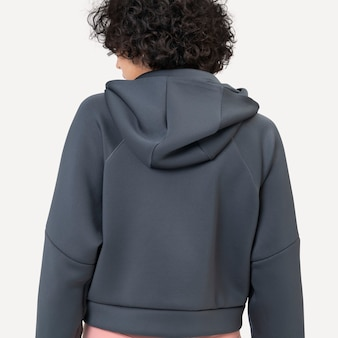 Mujer vistiendo sudadera con capucha gris para sesión de estudio de moda de invierno vista trasera