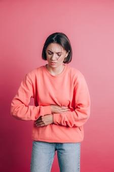 Mujer vistiendo un suéter casual en el fondo que sufre dolor de estómago con muecas dolorosas, sintiendo calambres repentinos, concepto de ginecología