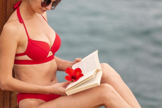 Mujer vistiendo traje de baño y libro de lectura