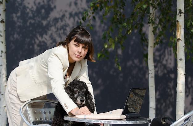 Mujer vistiendo un traje blanco sosteniendo a su perro y usando su computadora portátil sobre la mesa