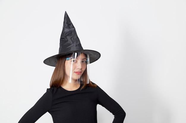 Mujer vistiendo traje de bruja y máscara de protección facial para halloween