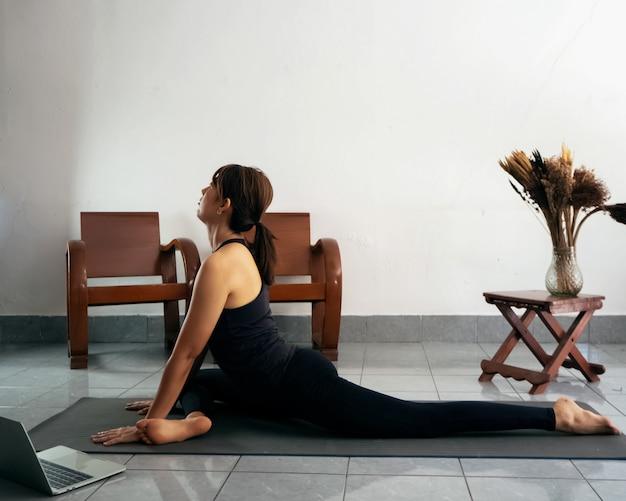 Mujer vistiendo traje de ejercicio, estirando el cuerpo sobre una estera de yoga, aprendiendo de forma portátil, en casa