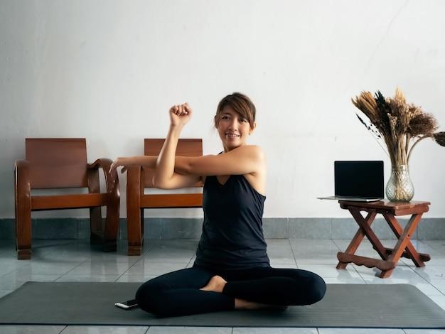 Mujer vistiendo traje de ejercicio estirando el cuerpo sobre una estera de yoga en casa, tiempo de relajación