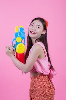 Una mujer se vistió en una ropa popular tailandesa tradicional que sostenía un arma de agua en un fondo rosado.
