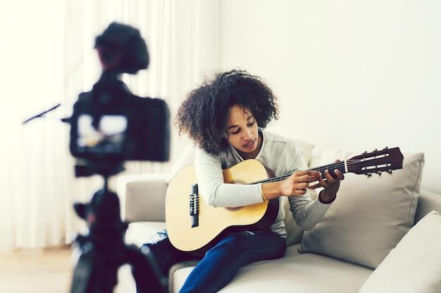Mujer vlogger filmando ella misma tocando una guitarra