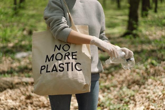 Mujer voluntaria es limpiada en el bosque mujer recolecta plástico
