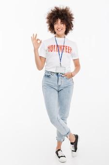 Mujer voluntaria feliz con insignia de pie y mostrando gesto ok