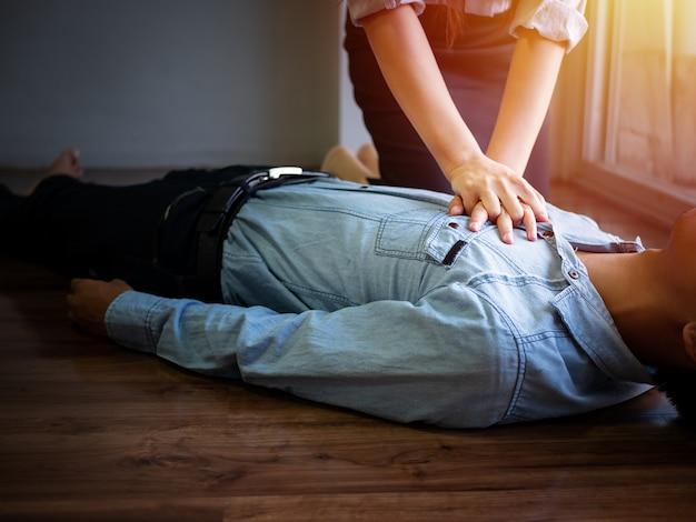 Mujer voluntaria de la oficina utiliza bomba manual en el pecho para primeros auxilios rcp de emergencia