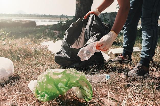 Mujer voluntaria recogiendo plástico de basura para limpiar en el parque del río