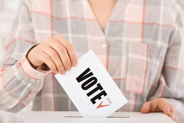Mujer votando cerca de las urnas, primer plano