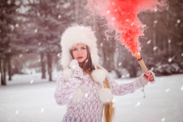 Mujer en winter park con bomba de humo rojo