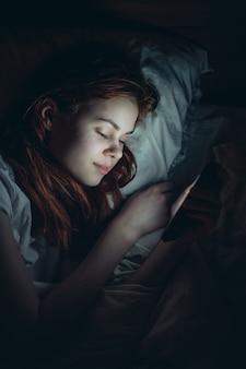 La mujer yace en la cama antes de irse a la cama con el teléfono en las manos, comunicación, estilo de vida, ocio