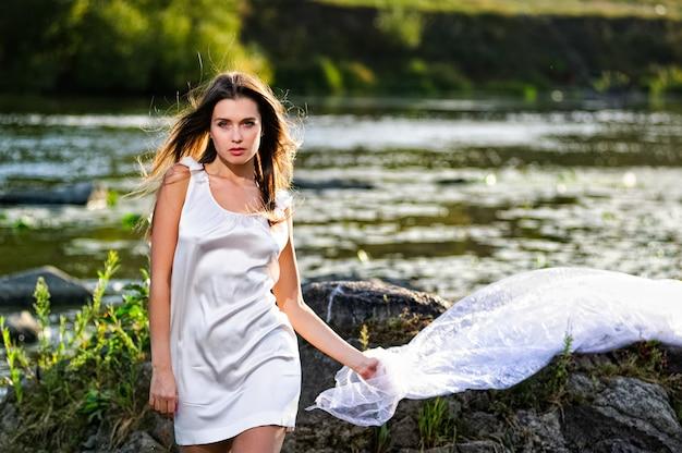 Mujer yang posando en el río al atardecer.
