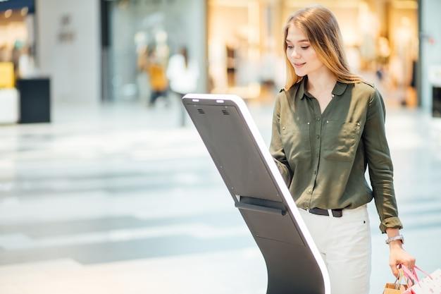 Mujer yendo de compras. buscando en el tablero de información con el mapa del centro comercial