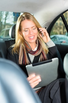 Mujer yendo en taxi, ella está hablando por teléfono