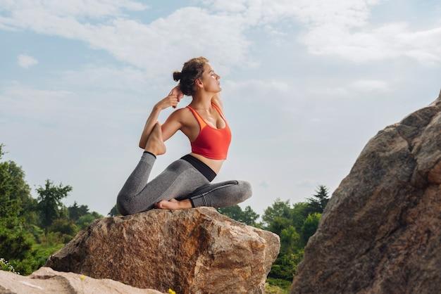 Mujer de yoga con experiencia en forma y delgada mostrando asanas de yoga mientras está sentado sobre una roca en el bosque