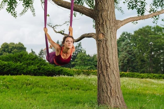 Mujer de yoga profesional experimentada con cuerpo muscular mostrando asanas de yoga de mosca