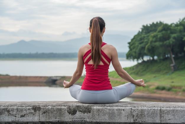 Mujer de la yoga que hace la meditación en el lago, visión trasera.