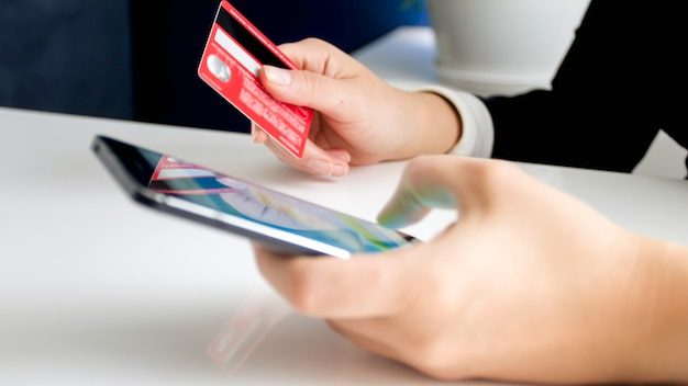 Mujer de yougn con tarjeta de crédito, navegación tienda online en smartphone. concepto de comercio electrónico y compras online.