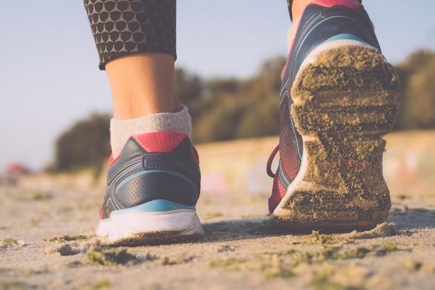 Mujer en zapatillas de deporte caminando en la playa en una mañana soleada, primer plano